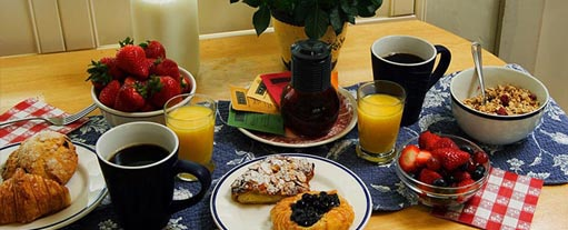 An image a table containing cofee, croissants, strawberries, orange juice, cerials, a bowl of fruit and some milk.